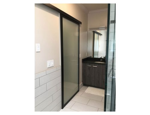 Contemporary barn door sliding system features our top-sliding DN80 sliding hardware, AF011 onyx frame and satin glass.